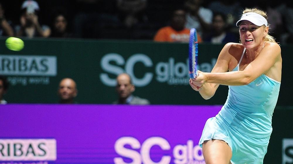 Maria Sharapova of Russia returns the ball to Agnieszka Radwanska of Poland during the Women's Tennis Association (WTA) final in Singapore on October 25, 2015. AFP PHOTO / MOHD FYROL