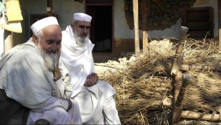 Pakistani tribal elders sit next to rubble of houses following an earthquake in Lower Dir on October 27, 2015. Rescuers were picking their way through rugged terrain and pockets of Taliban insurgency in the search for survivors after a massive quake hit Pakistan and Afghanistan, killing nearly 300 people. The toll was expected to rise as search teams reach remote areas that were cut off by the powerful 7.5 magnitude quake, which triggered landslides and stampedes as it toppled buildings and severed communication lines. AFP PHOTO / EHSAN ULLAH