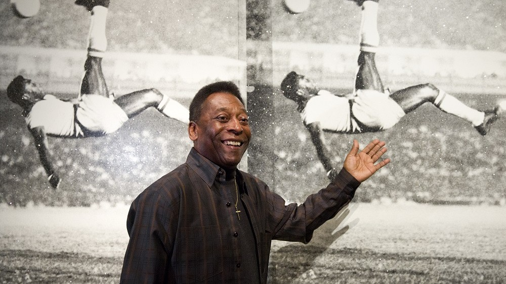 """Brazilian football legend Pele poses for photographers in front of a painting entitled """"Pele, Bicycle Kick"""" by artist Russell Young, during a press preview to promote the forthcoming exhibition """"Pele: Art, Life, Football"""" at the Halcyon Gallery in London on September 22, 2015. The exhibition, which features works from artists Andy Warhol, Lorenzo Quinn, Pedro Paricio, will also feature memorabilia from the course of Pele's career, including his first football. Pele: Art, Life, Football is set to run until October 18, 2015.   AFP PHOTO / JUSTIN TALLIS  RESTRICTED TO EDITORIAL USE, MANDATORY MENTION OF THE ARTIST UPON PUBLICATION, TO ILLUSTRATE THE EVENT AS SPECIFIED IN THE CAPTION"""