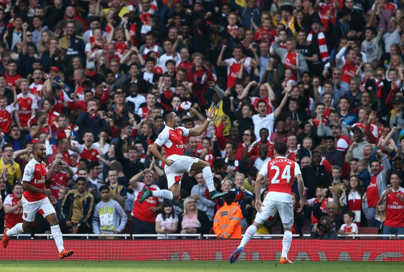 """Arsenal's Chilean striker Alexis Sanchez (C) celebrates scoring his goal with team mates Arsenal's German midfielder Arsenal's English midfielder Theo Walcott (L) during the English Premier League football match between Arsenal and Manchester United at the Emirates Stadium in London on October 4, 2015.    AFP PHOTO / JUSTIN TALLIS  RESTRICTED TO EDITORIAL USE. No use with unauthorised audio, video, data, fixture lists, club/league logos or """"live"""" services. Online in-match use limited to 45 images, no video emulation. No use in betting, games or single club/league/player publications."""