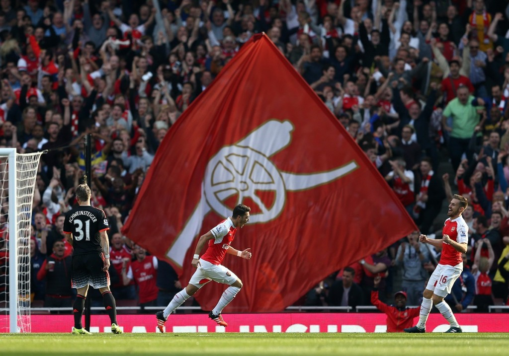 """Arsenal's German midfielder Mesut Ozil (C) celebrates with team mate Arsenal's Welsh midfielder Aaron Ramsey after scoring during the English Premier League football match between Arsenal and Manchester United at the Emirates Stadium in London on October 4, 2015.    AFP PHOTO / JUSTIN TALLIS  RESTRICTED TO EDITORIAL USE. No use with unauthorised audio, video, data, fixture lists, club/league logos or """"live"""" services. Online in-match use limited to 45 images, no video emulation. No use in betting, games or single club/league/player publications."""
