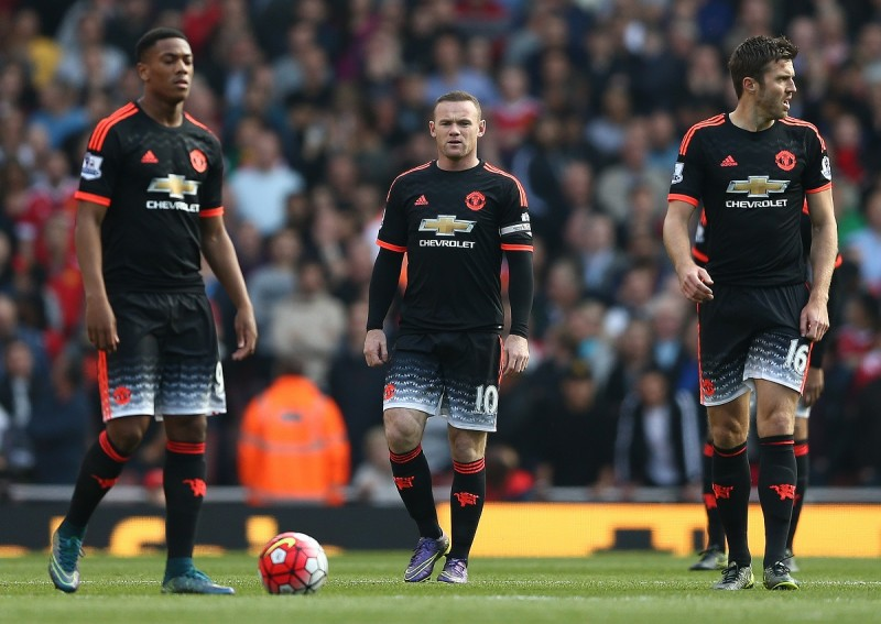 """Manchester United's English striker Wayne Rooney (C) reacts with team mates during the English Premier League football match between Arsenal and Manchester United at the Emirates Stadium in London on October 4, 2015.    AFP PHOTO / JUSTIN TALLIS  RESTRICTED TO EDITORIAL USE. No use with unauthorised audio, video, data, fixture lists, club/league logos or """"live"""" services. Online in-match use limited to 45 images, no video emulation. No use in betting, games or single club/league/player publications."""