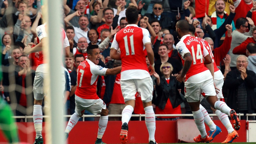 """Arsenal's Chilean striker Alexis Sanchez (2L) celebrates his first goal during the English Premier League football match between Arsenal and Manchester United at the Emirates Stadium in London on October 4, 2015.    AFP PHOTO / IKIMAGES  RESTRICTED TO EDITORIAL USE. No use with unauthorised audio, video, data, fixture lists, club/league logos or """"live"""" services. Online in-match use limited to 45 images, no video emulation. No use in betting, games or single club/league/player publications."""