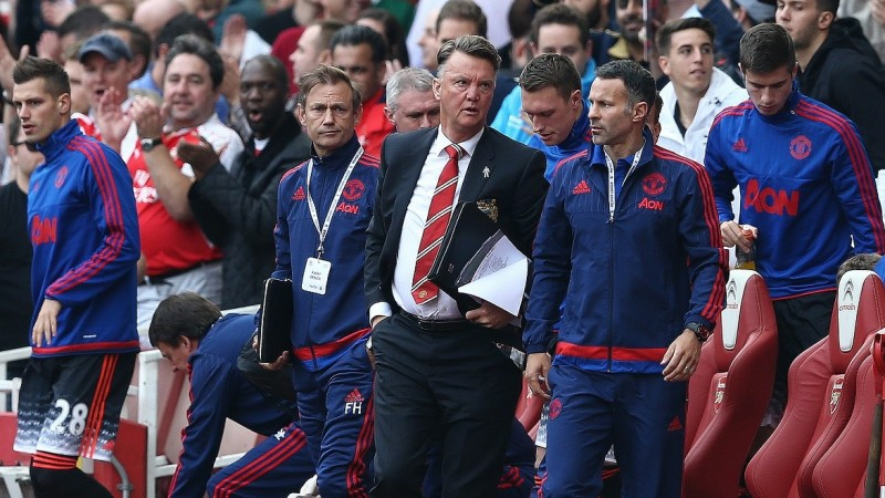 """Manchester United's Dutch manager Louis van Gaal (C) talks with Manchester United's Welsh assistant manager Ryan Giggs in the dug out during the English Premier League football match between Arsenal and Manchester United at the Emirates Stadium in London on October 4, 2015.    AFP PHOTO / JUSTIN TALLIS  RESTRICTED TO EDITORIAL USE. No use with unauthorised audio, video, data, fixture lists, club/league logos or """"live"""" services. Online in-match use limited to 45 images, no video emulation. No use in betting, games or single club/league/player publications."""
