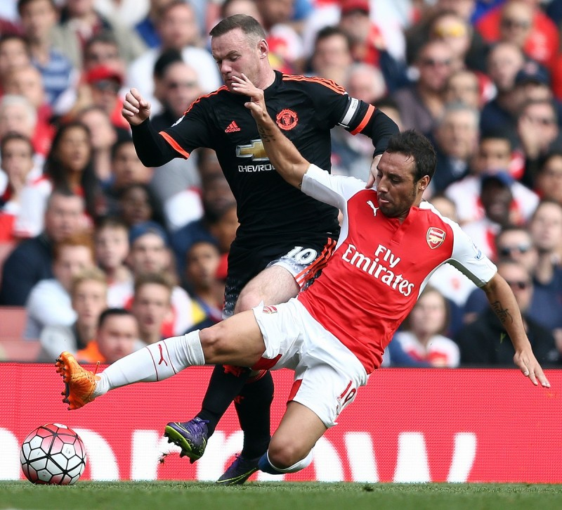 """Manchester United's English striker Wayne Rooney (L) vies against Arsenal's Spanish midfielder Santi Cazorla during the English Premier League football match between Arsenal and Manchester United at the Emirates Stadium in London on October 4, 2015.    AFP PHOTO / JUSTIN TALLIS  RESTRICTED TO EDITORIAL USE. No use with unauthorised audio, video, data, fixture lists, club/league logos or """"live"""" services. Online in-match use limited to 45 images, no video emulation. No use in betting, games or single club/league/player publications."""