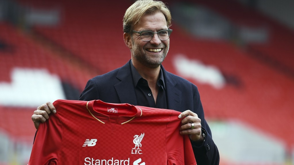 """Liverpool's new German manager Jurgen Klopp poses with a team jersey after a press conference to announce his new appointment at Anfield in Liverpool, northwest England, on October 9, 2015. Klopp described his job as """"the biggest challenge"""" in world football on October 9 following his appointment as the successor to Brendan Rodgers. Former Borussia Dortmund head coach Klopp, 48, was appointed on October 8 on a three-year contract following the dismissal of Rodgers, who was sacked October 4 after three and a half years at the club.  AFP PHOTO / PAUL ELLIS    RESTRICTED TO EDITORIAL USE. No use with unauthorized audio, video, data, fixture lists, club/league logos or 'live' services. Online in-match use limited to 75 images, no video emulation. No use in betting, games or single club/league/player publications."""