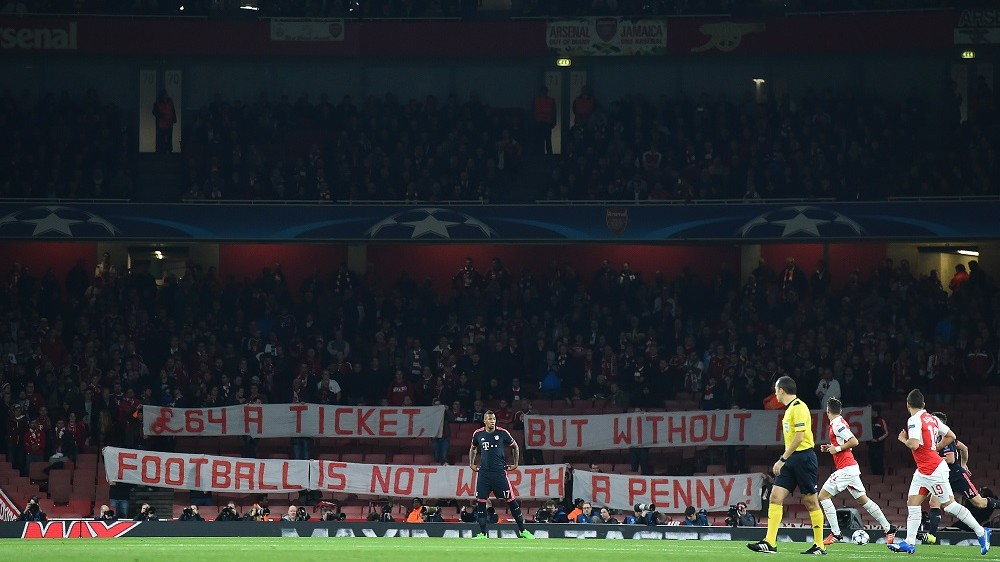 Bayern Munich fans hold a banner as they protest in the stands against the cost of tickets, at the beginning of the UEFA Champions League football match between Arsenal and Bayern Munich at the Emirates Stadium in London, on October 20, 2015.    AFP PHOTO / BEN STANSALL