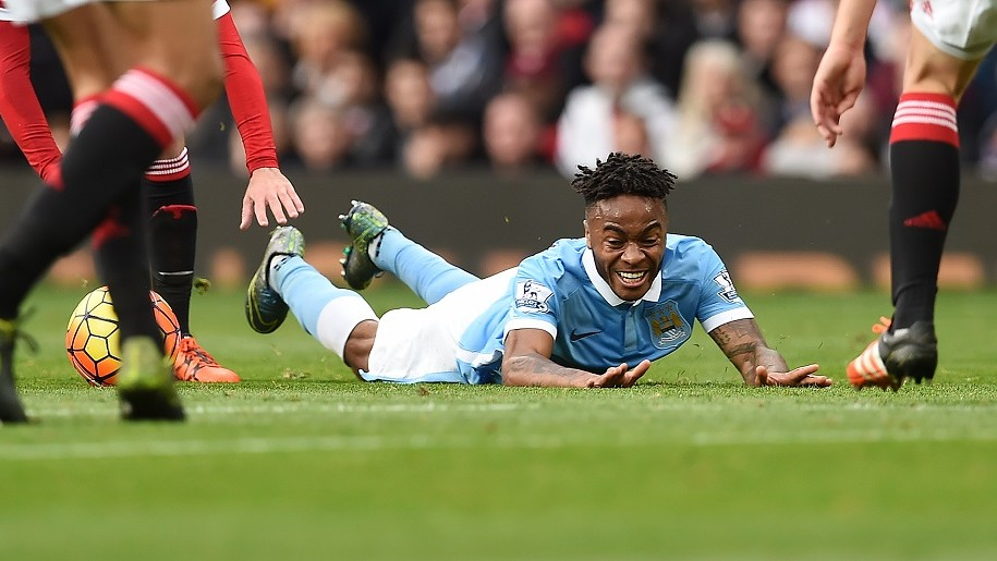 Manchester City's English midfielder Raheem Sterling (Below) falls as he plays during the English Premier League football match between Manchester United and Manchester City at Old Trafford in Manchester, north west England, on October 25, 2015.  AFP PHOTO / PAUL ELLIS  RESTRICTED TO EDITORIAL USE. No use with unauthorized audio, video, data, fixture lists, club/league logos or 'live' services. Online in-match use limited to 75 images, no video emulation. No use in betting, games or single club/league/player publications.