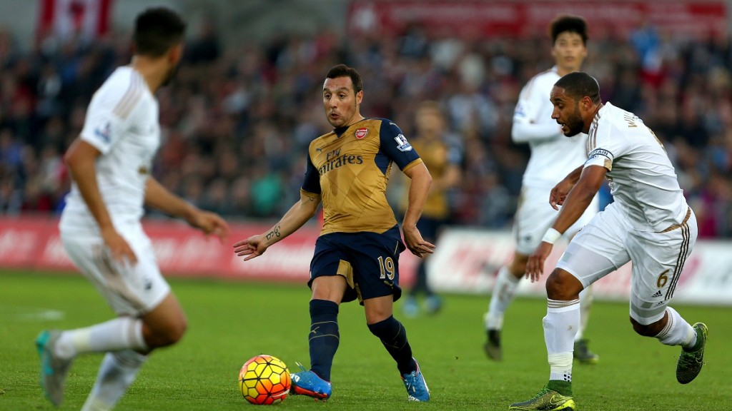 Arsenal's Spanish midfielder Santi Cazorla (2nd L) passes the ball during the English Premier League football match between Swansea City and Arsenal at The Liberty Stadium in Swansea, south Wales on October 31, 2015. Arsenal won the game 3-0. AFP PHOTO / GEOFF CADDICK  RESTRICTED TO EDITORIAL USE. No use with unauthorized audio, video, data, fixture lists, club/league logos or 'live' services. Online in-match use limited to 75 images, no video emulation. No use in betting, games or single club/league/player publications.