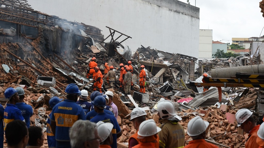 Firefighter rescue teams search for victims after an explosion swept two restaurants and a pharmacy in a suburban neighbourhood of Rio de Janeiro, on October 19, 2015. A powerful explosion suspected to be caused by illegally stockpiled gas canisters ripped through a Rio de Janeiro neighbourhood Monday, injuring at least seven people and destroying homes and businesses. Footage on Globo television from the Sao Cristovao area of northern Rio, in a neighborhood near the giant Maracana stadium, showed firefighters dousing flames and clawing through piles of twisted metal and rubble searching for survivors.  AFP PHOTO / VANDERLEI ALMEIDA