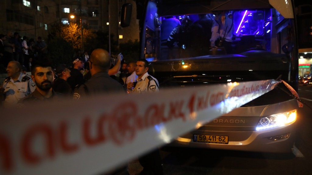 """Israeli police gather at the scene where an Arab man on a Jerusalem bus stabbed an off-duty Israeli soldier and tried to grab his weapon, lightly wounding him, before being shot dead by security forces, on October 12, 2015 in Jerusalem. Prime Minister Benjamin Netanyahu vowed that Israel would not bow to """"knife terror"""" while four stabbings in Jerusalem gave no sign of Palestinian unrest slowing.  AFP PHOTO / GALI TIBBON"""