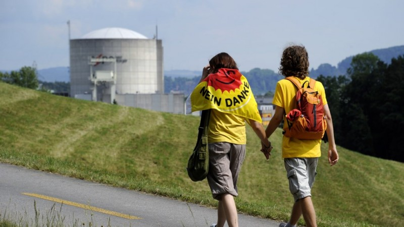 Two young activits walk by the Beznau nuclear power plant, the oldest in Switzerland, during an anti-nuclear protest march on May 22, 2011 in Doettingen. More thant 10,000 people took part in the demonstration against nuclear power in northern Switzerland, in anticipation of the Swiss government's decision next week on the use of nuclear power in the future.  AFP PHOTO / FABRICE COFFRINI