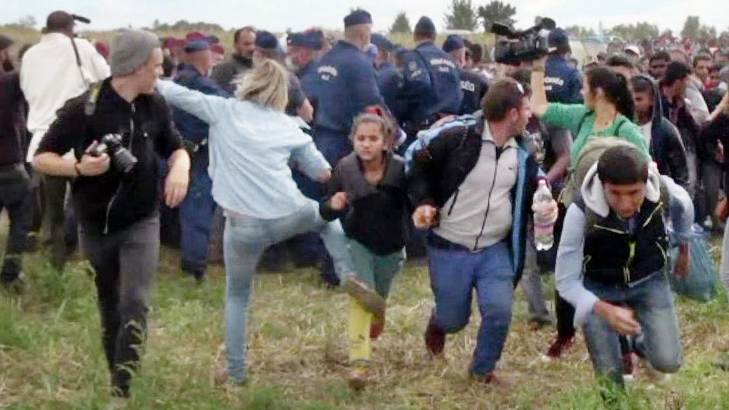 This video grab made on September 9, 2015 shows a Hungarian TV camerawoman kicking a child as she run with other migrants from a police line during disturbances at Roszke, southern Hungary. After the footage appeared, the camerawomen was fired on September 8 by N1TV, an internet-based TV station close to Hungary's far-right Jobbik party. The woman, later named as Petra Laszlo, can be seen tripping a man sprinting with a child in his arms, and kicking another running child in two separate incidents. The scenes took place as hundreds of migrants broke through a police line at a collection point close to the Serbian border where thousands have been crossing over each day for the past month.     AFP PHOTO / INDEX.HU