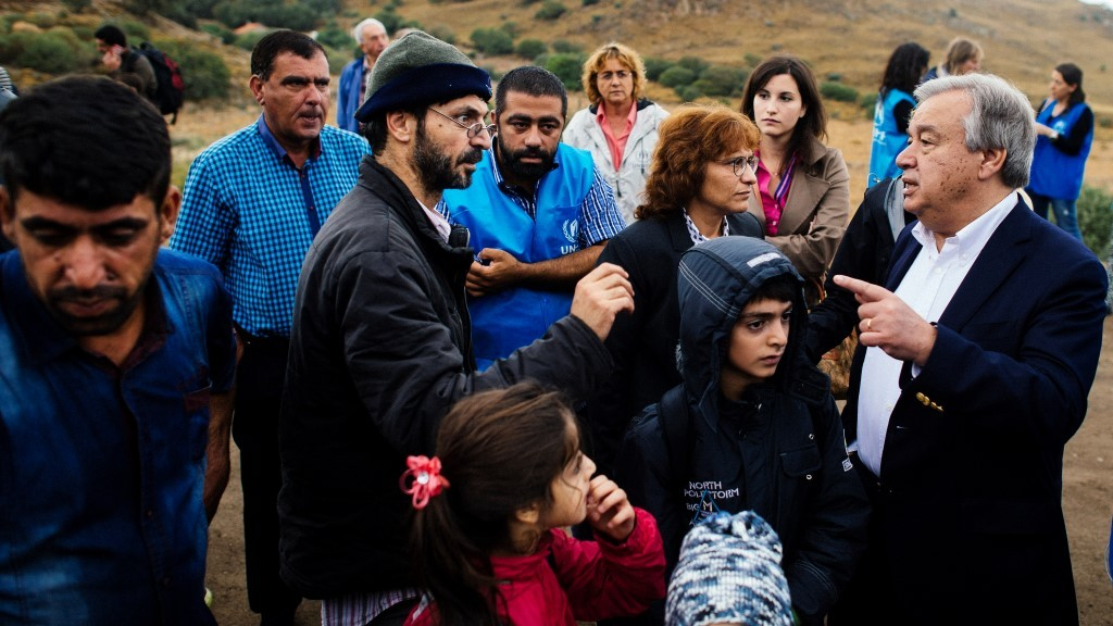 The head of the UN refugee agency (UNHCR) Antonio Guterres (R) meets with people on a road shortly after they arrived with other migrants and refugees by boat on the Greek island of Lesbos after crossing the Aegean sea from Turkey on October 11, 2015. Greece pledged on October 10 during talks with its EU partners to open its first so-called hotspot reception centre on the island of Lesbos within 10 days under EU efforts to better deal with the massive influx of migrants. AFP PHOTO / DIMITAR DILKOFF