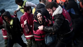 Refugees and migrants disembark from a dinghy on the Greek island of Lesbos, on October 28, 2015, after crossing the Aegean sea from Turkey. At least five migrants including three children, died on October 28, 2015 after four boats sank between Turkey and Greece, as rescue workers searched the sea for dozens more, the Greek coastguard said. The new accidents brought to 34 the number of migrants found dead in Greek waters this month, according to an AFP tally based on data from Greek port police. Since the start of the year, 560,000 migrants and refugees have arrived in Greece by sea, out of over 700,000 who have reached Europe via the Mediterranean, according to the International Office for Migration (IOM). AFP PHOTO / ANGELOS TZORTZINIS
