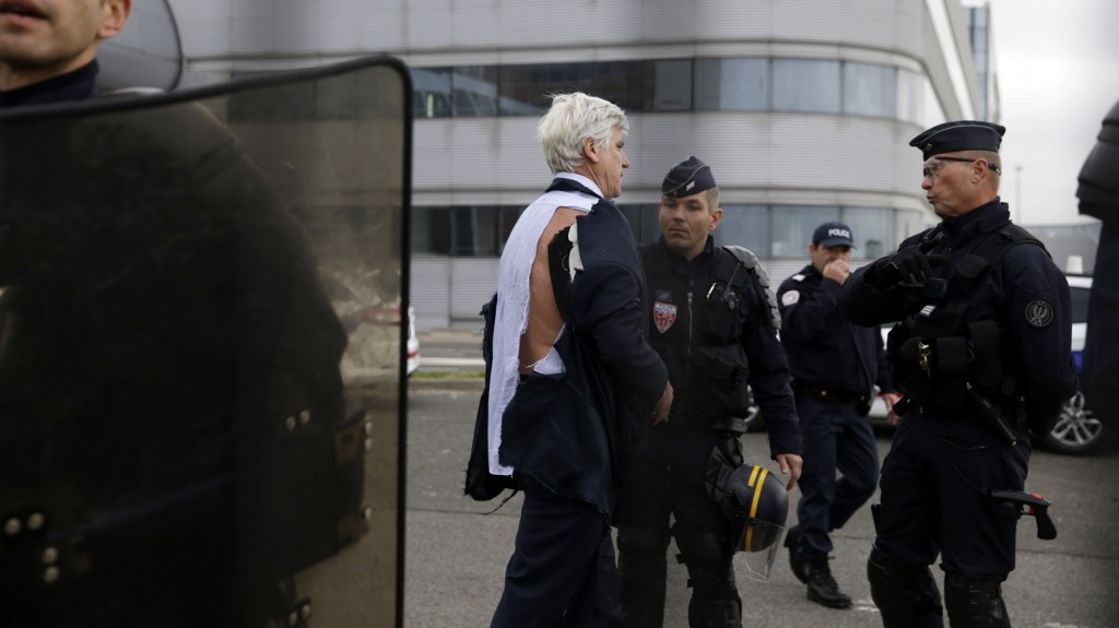 Director of Air France in Orly Pierre Plissonnier, nearly shirtless, stands behind a fence, flanked by anti-riot police officers, after several hundred of employees invaded the offices of Air France, interrupting the meeting of the Central Committee (CCE) in Roissy-en-France, on October 5, 2015. Air France-KLM unveiled a revamped restructuring plan on October 5 that could lead to 2,900 job losses after pilots for the struggling airline refused to accept a proposal to work longer hours. AFP PHOTO / KENZO TRIBOUILLARD