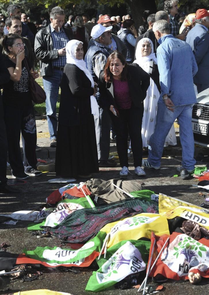 Ankara, 2015. október 10.  Az áldozatok zászlókkal letakart holttestei hevernek a kettõs robbantásos merénylet helyszínén egy béketüntetés gyülekezõhelyén Ankarában 2015. október 10-én. A török fõvárosban elkövetett merényletnek legalább harminc halálos áldozata és mintegy 126 sebesültje van. A menet résztvevõi az ország délkeleti részén a török állam és kurd fegyveresek között zajló konfliktus ellen terveztek tiltakozni. (MTI/AP)