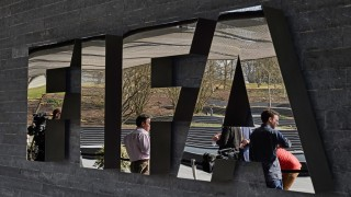 Member of the media wait next to a logo of the World's football governing body, at the FIFA headquarters in Zurich, prior to a press conference of FIFA President Sepp Blatter on March 20, 2015, closing a two-day meeting to decide the dates of the 2022 World Cup in Qatar. AFP PHOTO / MICHAEL BUHOLZER