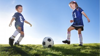 Young Soccer Players Kicking Ball