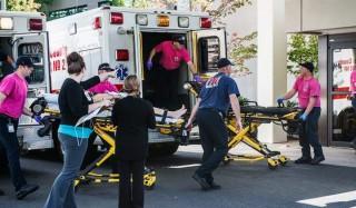 Roseburg, 2015. október 1. Az Umpqua fõiskolában történt lövöldözés egyik sérültjét viszik mentõsök az Oregon állambeli Roseburg egyik kórházába 2015. október 1-jén. A támadásban legkevesebb tizenöten életüket vesztették, húszan pedig megsebesültek. (MTI/AP/Roseburg News-Review/Aaron Yost)