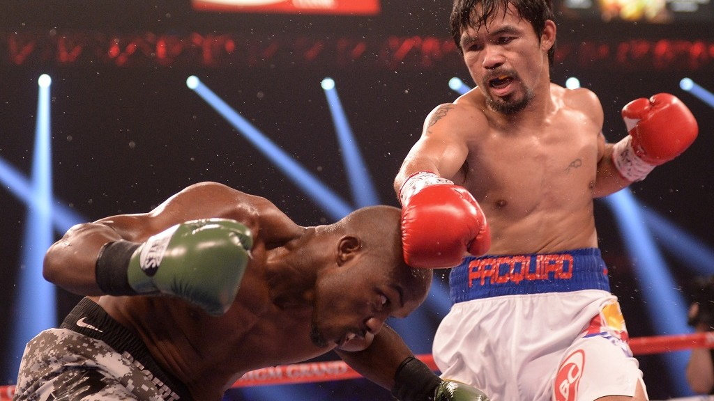 (FILES) This file photo taken on April 12, 2014 shows Manny Pacquiao of the Philippines (R) in action against Timothy Bradley (L) of the US during their WBO World Welterweight Championship title match at the MGM Grand Arena in Las Vegas. Philippine boxing hero Manny Pacquiao announced October 7, 2015 he would likely retire next year after one last fight to focus on a career in politics, hopefully as a senator.    AFP PHOTO / FILES / JOE KLAMAR