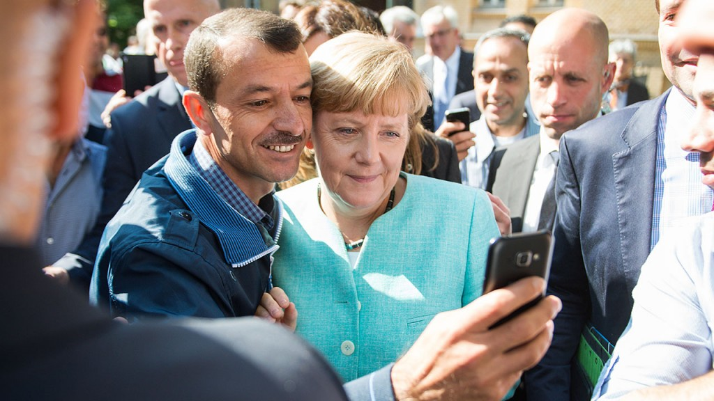 Asylum seeker (C, L) takes a selfie picture with German Chancellor Angela Merkel (C, R) following Merkel's visit at a branch of the Federal Office for Migration and Refugees and a camp for asylum-seekers in Berlin on September 10, 2015. Around 450,000 refugees have arrived in Germany so far this year, including 37,000 in the first eight days of September, Vice Chancellor Sigmar Gabriel told parliament on Thursday. Chancellor Angela Merkel has urged the 28-nation bloc to go further and agree on a proportional distribution of refugees with no limits on actual numbers, amid a record influx from war-torn Syria and other countries. AFP PHOTO / DPA / BERND VON JUTRCZENKA +++ GERMANY OUT