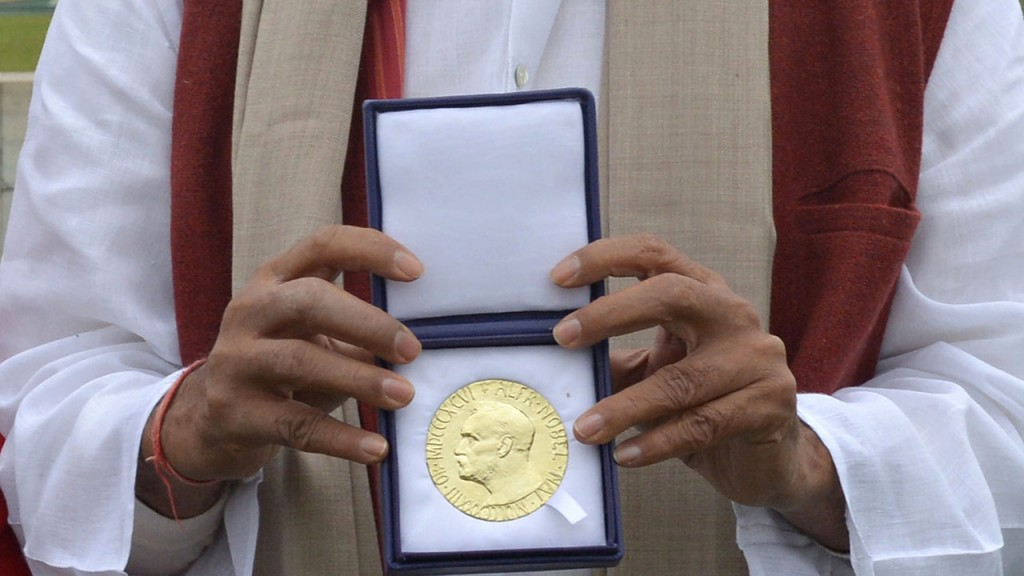 Indian Nobel Peace Prize winner Kailash Satyarthi poses with his Nobel medal after paying tribute at Raj Ghat, the memorial for India's founding father Mahatma Gandhi, in New Delhi on December 14, 2014. Satyarthi, 60, who for 35 years fought to free thousands of children from virtual slave labour, was on December 10 jointly awarded the Nobel Peace Prize with Malala Yousafzai, the Pakistani teenage education campaigner shot by the Taliban in 2012. AFP PHOTO / SAJJAD HUSSAIN
