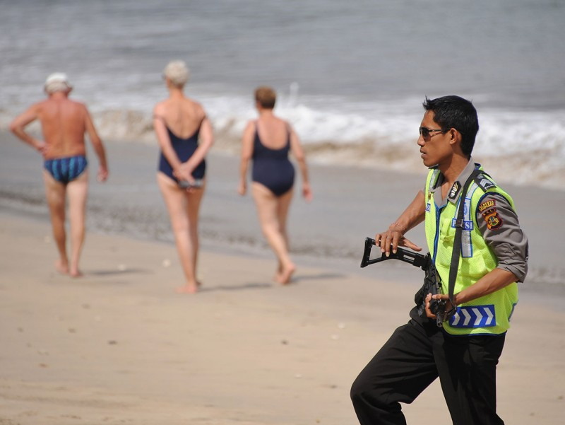 An Indonesian police officer stands guard as foreign tourists walk past in front the Nyoman Cafe on a beach in Jimbaran on Bali island on October 1, 2012, on the seventh anniversary of the 01 October 2005 bomb blasts. On 1 October 2005, bomb blasts ripped through Manega and Nyoman Cafes in Jimbaran and Raja's bar in Kuta, killing at least 24 people, including one Australian. AFP PHOTO / SONNY TUMBELAKA