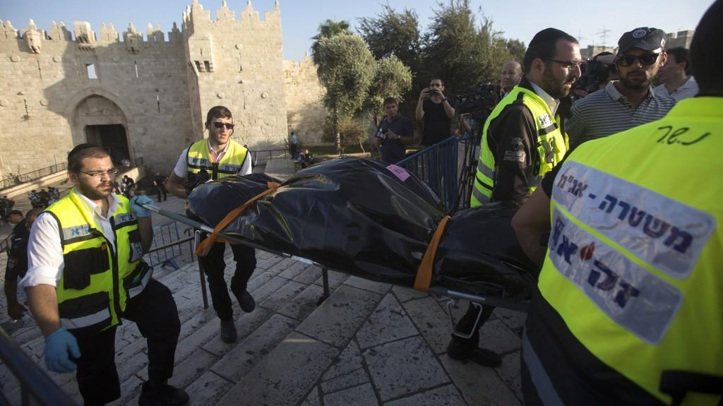 Jeruzsálem, 2015. október 14. Izraeli mentõsök viszik annak a lelõtt palesztin merénylõnek a holttestét, aki megpróbált leszúrni egy embert a Jeruzsálemben óvárosában lévõ Damaszkuszi kapunál 2015. október 14-én. (MTI/EPA/Atef Szafadi)