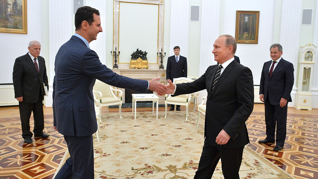 """Russian President Vladimir Putin (R) greets his Syrian counterpart Bashar al-Assad (L) during a meeting at the Kremlin in Moscow on October 20, 2015. Assad, on his first foreign visit since Syria's war broke out, told his main backer and counterpart Putin in Moscow that Russia's campaign in Syria has helped contain """"terrorism"""". AFP PHOTO / RIA NOVOSTI / KREMLIN POOL / ALEXEY DRUZHININ"""