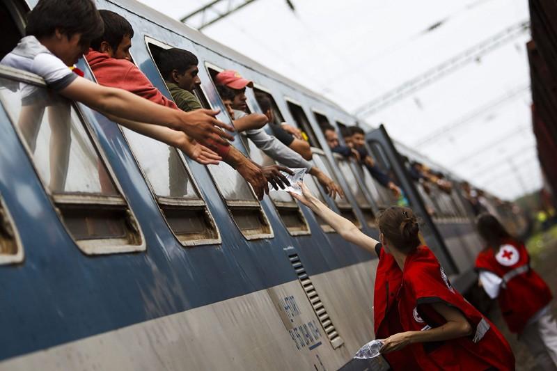 Zákány, 2015. szeptember 22.A Magyar Vöröskereszt aktivistája zacskós vizet ad illegális bevándorlónak a Gyékényes vasútállomáson, Zákányban 2015. szeptember 22-én. A migránsok vonattal érkeztek a horvátországi Felsőtárnokról (Tovarnik). A somogyi határtelepülés az utóbbi négy napban több mint 12 ezer embert fogadott, hogy tovább tudjanak menni a regisztrációs pontokra.MTI Fotó: Varga György