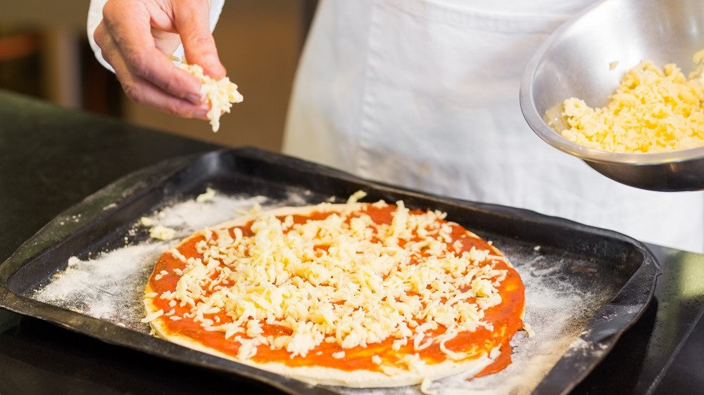 Mid section of a chef preparing pizza