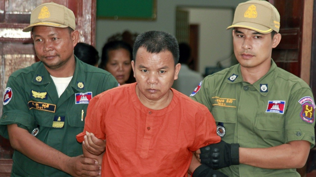 Yem Chroeum (C), 55, is escorted by Cambodian police officials at a court in Battambang province on October 20, 2015. An unlicensed Cambodian doctor who allegedly infected more than 200 people with HIV, including some who later died, went on trial for murder on October 20. AFP PHOTO