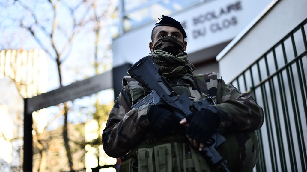 A French soldier stands guard in front of a school in the 20th rrondissement of Paris on November 22, 2015, following a coordinated wave of attacks on Parisian nightspots claimed by Islamic State group (IS) jihadists that killed 130 people. AFP PHOTO / LOIC VENANCE / AFP / LOIC VENANCE