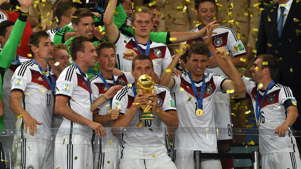 Germany's forward Lukas Podolski (front-C) holds up the World Cup trophy as he celebrates with his teammates after winning the 2014 FIFA World Cup final football match between Germany and Argentina 1-0 following extra-time at the Maracana Stadium in Rio de Janeiro, Brazil, on July 13, 2014.    AFP PHOTO / PEDRO UGARTE