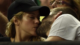 FC Barcelona's defender Gerard Pique (R) and his wife Colombian singer Shakira kiss during the 2014 FIBA World basketball championships quarter-final match Slovenia vs USA at the Palau Sant Jordi arena in Barcelona on September 9, 2014.  AFP PHOTO / LLUIS GENE