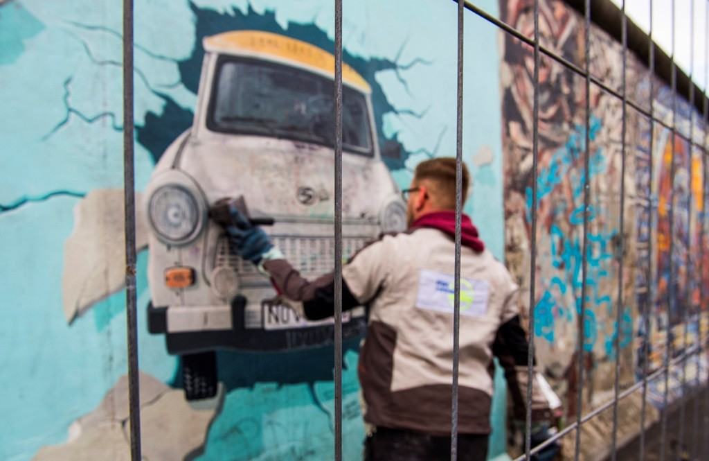 A worker removes graffiti from a painting behind a temporary fence on the East Side Gallery, a much-visited stretch of the Berlin wall, in Berlin on November 5, 2015. The city of Berlin has decided to erect a 80cm high permanent barrier to discourage people from defacing the works made by artists who decorated the yet untouched east side with artwork and political statements after the wall was taken down in 1989-1990. Though designated as a historical landmark, the paintings have yet again been covered in grafitti.   AFP PHOTO / JOHN MACDOUGALL