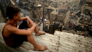 A boy looks at houses destroyed by a huge fire in a slum area in Mandaluyong City, suburban Manila on November 26, 2015. A huge fire that swept through a crowded Manila shanty town has razed more than 800 homes, leaving thousands homeless after they were forced to flee for their lives from the towering flames, officials said on November 26. AFP PHOTO / NOEL CELIS / AFP / NOEL CELIS