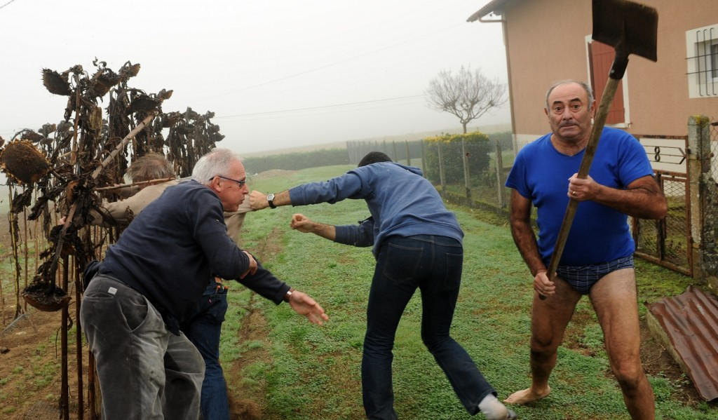 President of the Bird Protection league (LPO) Allain Bougrain-Dubourg (L) is evacuated by an inhabitant after clashing with the owner (R) of a plot where bird traps were found during an action against finch poaching, on November 9, 2015 in Audon, south western France. AFP PHOTO / GAIZKA IROZ