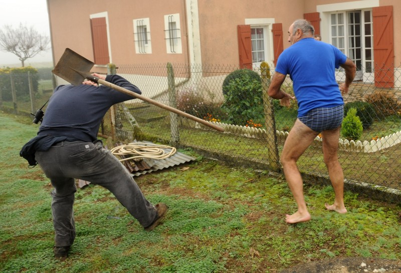 TOPSHOTS A militant of the Bird Protection league (LPO) (L) is hit by a spade thrown by the owner of a plot where bird traps were found during an action against finch poaching, on November 9, 2015 in Audon, south western France. AFP PHOTO / GAIZKA IROZ
