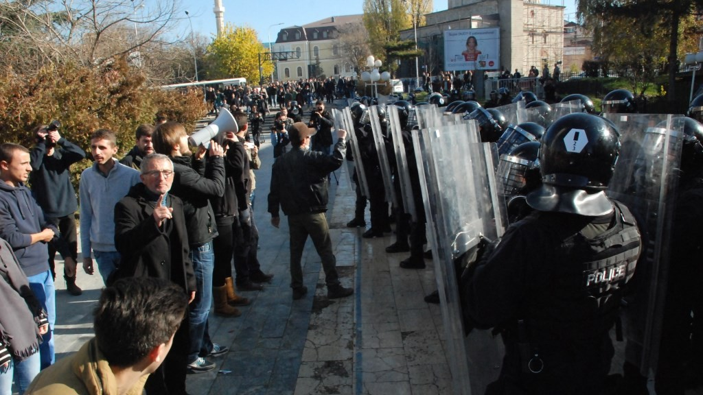 PRISTINA, KOSOVO - NOVEMBER 17: Kosovo's police officers take cover during clashes with supporters of opposition parties near the Kosovo's parliament in Pristina on November 17, 2015. Few hundred supporters of the opposition political parties clashed outside of the building of Kosovo's Parliament as they protest against the agreements that has been reached during the EU-brokered dialogue with Serbia. Erkin Keci / Anadolu Agency