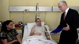 Budapest, 2015. november 6.Balog Zoltán, az emberi erőforrások minisztere (j) egy hétvégi pihenésre szóló meghívást ad át Fenyvesi Zsolt mentőápolónak, balra a beteg felesége az Országos Baleseti és Sürgősségi Intézetben, Budapesten 2015. november 6-án. A mentőápolót november 3-án betegszállítás közben hasba szúrta egy ellátásra szoruló férfi, amelynek következtében súlyos, életveszélyes hasi sérüléseket szenvedett.MTI Fotó: Bruzák Noémi