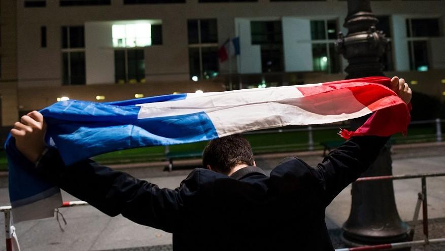Berlin, 2015. november 14. Egy francia zászlót tartó férfi áll Franciaország berlini nagykövetsége elõtt 2015. november 14-én kora hajnalban. A francia fõvárosban elõzõ este összehangoltan több merényletet követtek el, a támadásoknak legkevesebb 149 halálos áldozata van. Nyolc terrorista halt meg, közülük heten felrobbantották magukat. (MTI/EPA/Gregor Fisher)