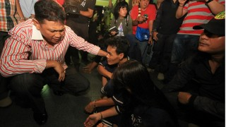 This picture taken in Bandar Lampung on November 15, 2015 shows Bandar Lampung Head police chief Edward Syah Pernong (L) speaking to suspected murderers Rudi Efendi (C) and his wife Nuriah (C front).  A newlywed Indonesian couple stands accused of dining on the genitals of a man believed to have raped a woman after her husband allegedly murdered him and cut off his private parts, police said on November 17.    AFP PHOTO / PERDIANSYAH