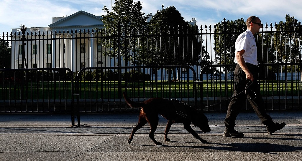 WASHINGTON, DC - SEPTEMBER 23:  A uniformed Secret Service officer patrols outside the White House on Pennsylvania Avenue with a member of the canine team on September 23, 2014 in Washington, DC.  An additional small fence has been added to the perimeter of the White House following an incident last week where a man jumped the fence and gained access to the interior of the building. (Photo by Win McNamee/Getty Images)