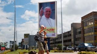 Nairobi, 2015. november 23. Ferenc pápa kenyai látogatását hirdetõ plakát turistákkal az elõtérben a Nairobi Jomo Kenyatta Nemzetközi Repülõtéren (JKIA) 2015. november 23-án, két nappal a katolikus egyházfõ látogatása elõtt. (MTI/EPA/Daniel Irungu)