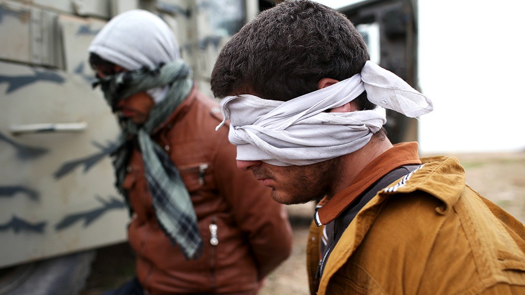 SINJAR, IRAQ - NOVEMBER 16:  Suspected ISIL or Daesh are detained by Kurdish Peshmerga forces after they fled their frontline village to a Kurdish-controlled area on November 16, 2015 to Sinjar, Iraq. Peshmerga forces carefully screened displaced Iraqis as they arrived, fearing enemy infiltrators and suicide bombers. Kurdish forces, with the aid of massive U.S.-led coalition airstrikes, liberated Sinjar from ISIL extremists, known in Arabic as Daesh, moving the frontline south. About one thousand villagers in Ghabosyeh fled north to Kurdish held territory, to take refugee camps or onward as refugees to Turkey or Europe.  (Photo by John Moore/Getty Images)