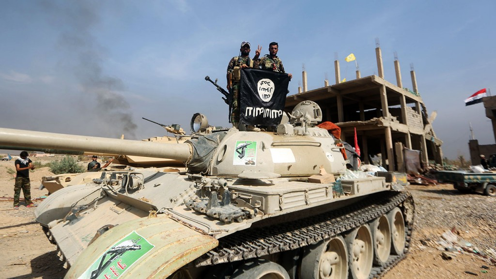 Iraqi Shiite fighters from the Popular Mobilisation units, fighting alongside Iraqi government forces, display, upside down, the flag of the Islamic State (IS) group during a military operation aimed at the centre of Baiji, some 200 kilometres north of Baghdad on October 19, 2015. Iraqi forces advanced on three fronts against the Islamic State group, flushing out pockets of resistance in and around Baiji and closing in on Ramadi and Hawijah, officers said. AFP PHOTO / AHMAD AL-RUBAYE / AFP / AHMAD AL-RUBAYE