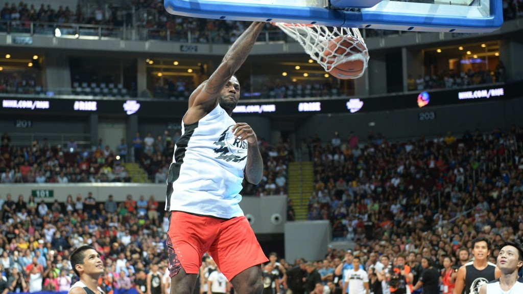 US NBA superstar LeBron James plays during an exhibition game as part of a clinic session in Manila on August 20, 2015. James is here to conduct basketball clinic to select talented baskeball players from disadvantaged families.    AFP PHOTO / TED ALJIBE