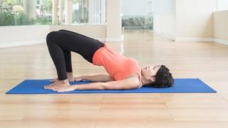 Asian woman make yoga Bridge pose in classroom